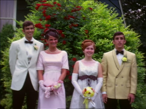 1960s two teen couples in formalwear posing by bushes outdoors / home movie - high school prom stock videos and b-roll footage