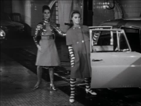 B/W 1960s two women modeling coat + dress next to car in car wash / newsreel