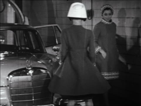 b/w 1960s two women modeling coats + hats next to car / one asian / newsreel - east asian ethnicity stock videos & royalty-free footage