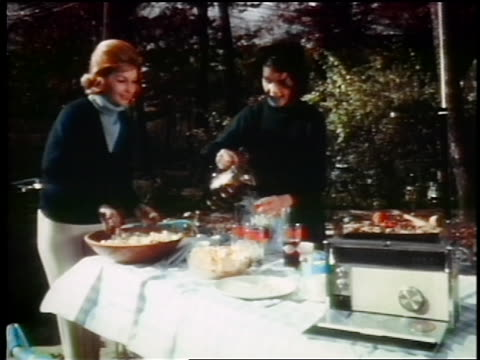 vidéos et rushes de 1960s two women preparing food for picnic + listening to radio / one woman stirs, the other pours - pique nique