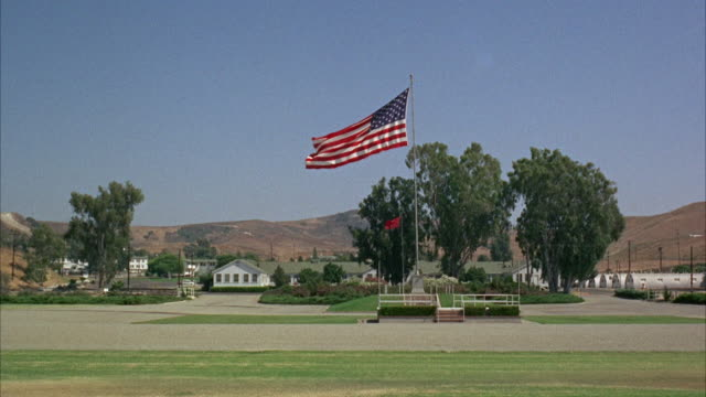 vidéos et rushes de 1960s ws united states flag on pole in marine base and training area - armée américaine