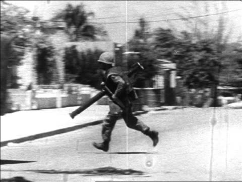 b/w 1960s us marine with bazooka running between tanks during revolution / dominican republic - イスパニョーラ点の映像素材/bロール