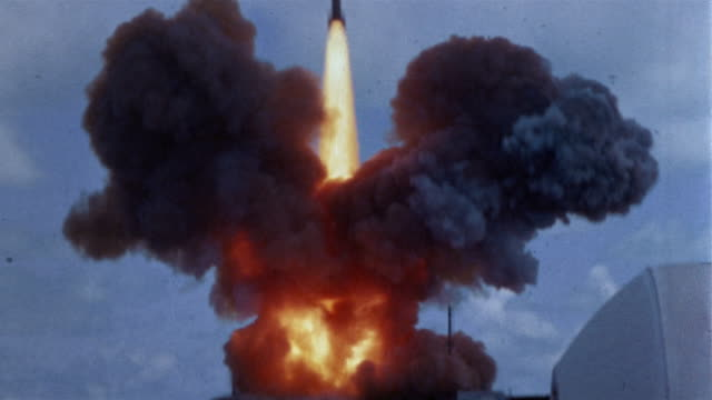 vídeos de stock e filmes b-roll de 1960s long shot boosters exploding / rocket taking off / tilt up rocket soaring through sky - guerra fria