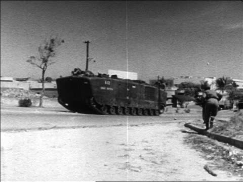 b/w 1960s us military transport moving on street during revolution / dominican republic - イスパニョーラ点の映像素材/bロール