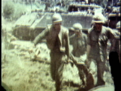 stockvideo's en b-roll-footage met 1960s ms us soldiers carrying wounded soldiers on stretchers toward and out of helicopters during vietnam war / vietnam - slachtoffer
