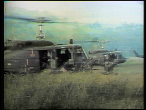 1960s us soldiers exiting helicopters in grass then helicopters taking off / vietnam war - vietnamkrieg stock-videos und b-roll-filmmaterial