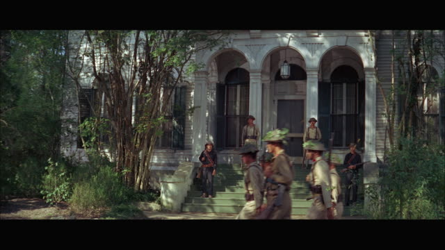 1960s ws viet cong soldiers on guard in front of house - ベトコン点の映像素材/bロール