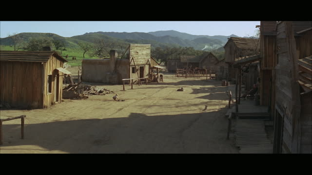 1960s ws cs western town with baby on street and riders in distance - wild west stock videos & royalty-free footage