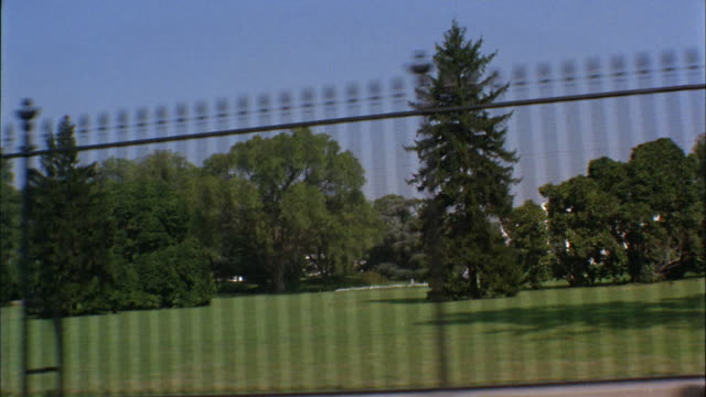 1960s wide shot car point of view passing fence outside white house - washington dc stock-videos und b-roll-filmmaterial