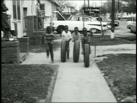 1960s wide shot group of black boys rolling car tires on sidewalk toward cam - rolling stock videos & royalty-free footage