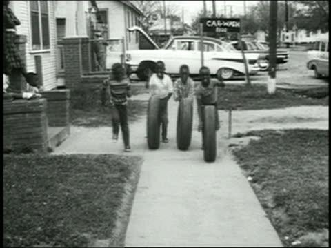 1960s wide shot group of black boys rolling car tires on sidewalk toward cam - 巻く点の映像素材/bロール