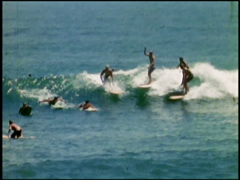 1960s wide shot group of surfers on one wave / colliding and falling / California
