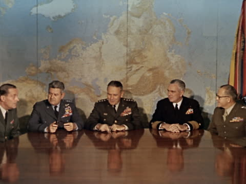 1960s wide shot joint chiefs of staff sitting at large shiny conference table with map in background - 将校点の映像素材/bロール