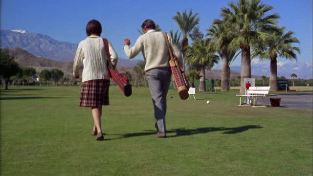 1960s wide shot man and woman walking away from cam on golf course + carrying clubs / arizona - ゴルフクラブ点の映像素材/bロール