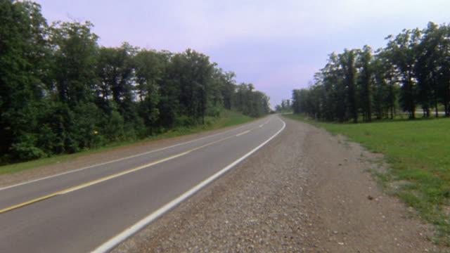 vídeos de stock, filmes e b-roll de 1960s wide shot man walking onto highway shoulder, taking off eyeglasses and sticking tongue out at camera - plano americano