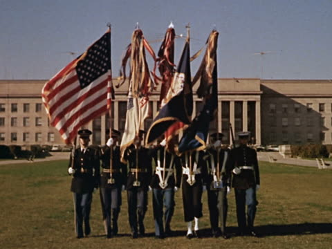 1960s wide shot marines walking away from the pentagon carrying us and armed forces flags / washington dc - 近衛兵点の映像素材/bロール