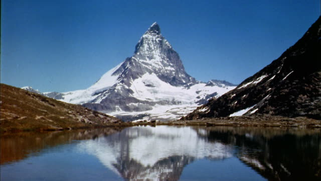 vídeos de stock e filmes b-roll de 1960s wide shot matterhorn mountain and lake in foreground / switzerland - suíça