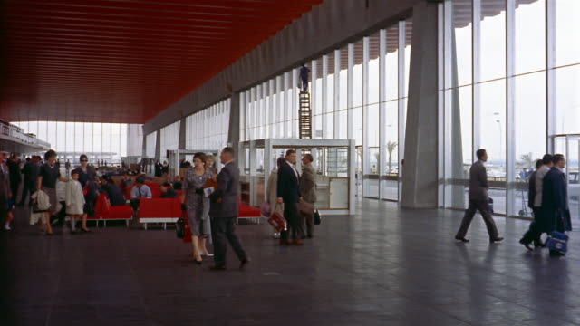 1960s wide shot pan passengers leaving airport terminal