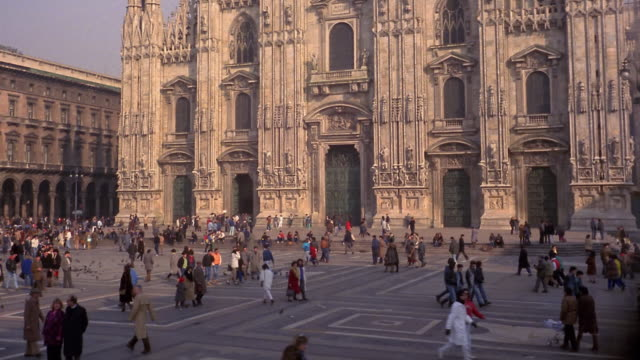 1960s wide shot people walking around outside duomo / milan, italy - milan stock videos & royalty-free footage