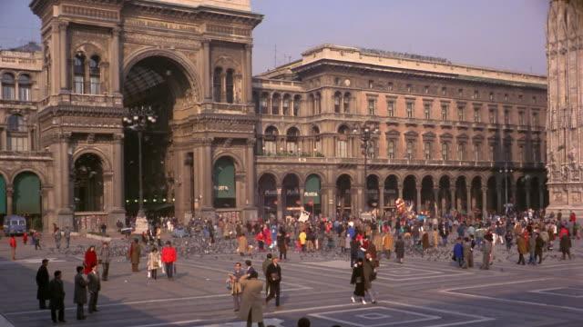 1960s wide shot people walking around Piazza del Duomo, flock of pigeons flying around / Milan