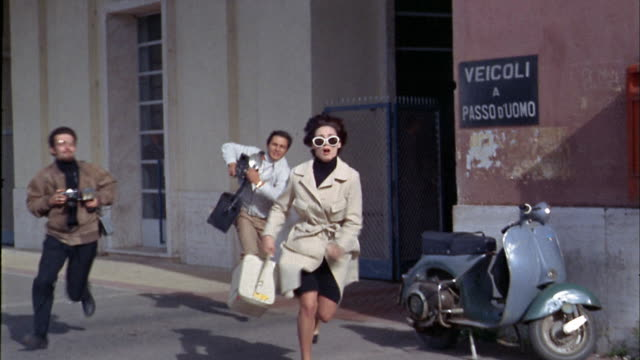 1960s wide shot photographers chasing woman leaving building / tearing her sunglasses off / Italy