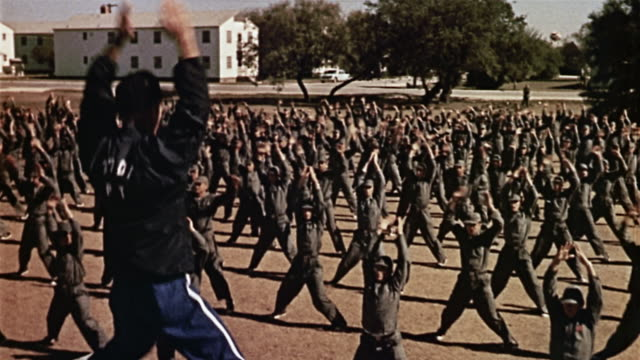 1960s wide shot soldiers doing jumping jacks during basic training - army stock-videos und b-roll-filmmaterial
