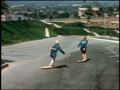 1960s wide shot tracking shot 2 boys in matching jackets skateboarding barefoot in parking lot / California