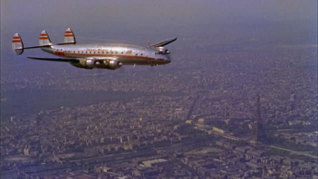 1960s wide shot tracking shot Constellation airplane flying over Paris w/Eiffel Tower