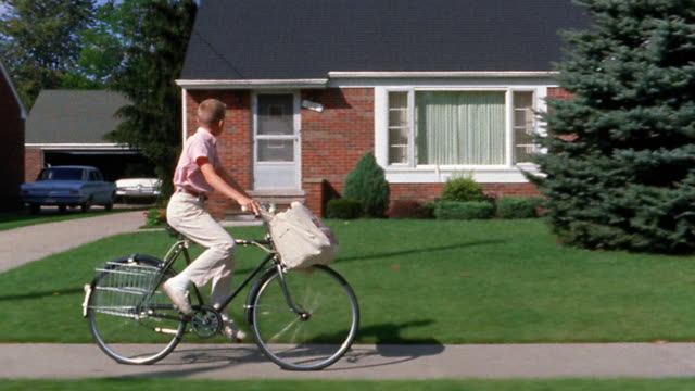 1960s wide shot tracking shot newspaper delivery boy riding bicycle and throwing papers onto front lawns of houses - lanciare video stock e b–roll