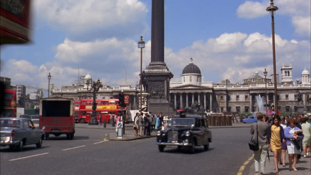 1960s wide shot traffic and pedestrians in trafalgar square with national gallery in background / london - 1960 stock videos & royalty-free footage