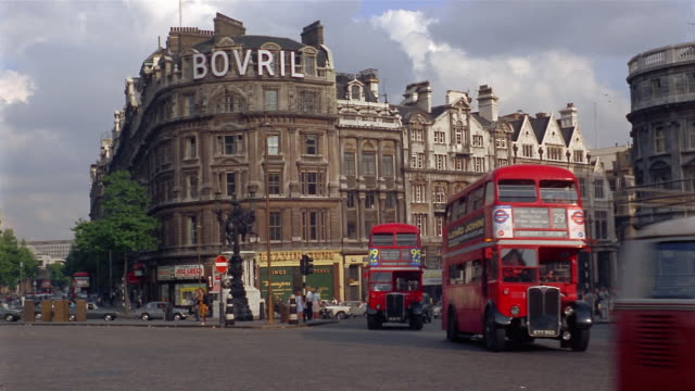 1960s wide shot traffic on busy street with Bovril sign on building in background / London, England
