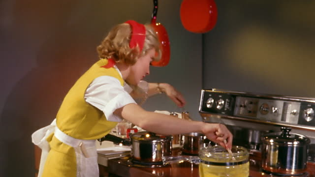 vídeos de stock e filmes b-roll de 1960s wide shot woman in yellow dress stirring and cooking food on stove while talking on telephone - multitarefas