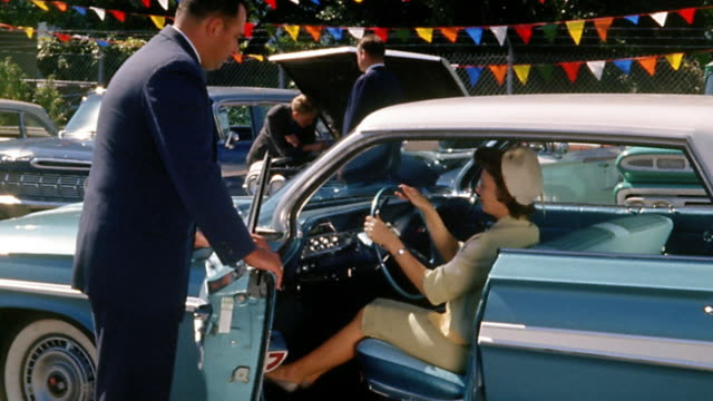 1960s wide shot woman testing seat and steering in parked car as salesman looks on - 自動車産業点の映像素材/bロール