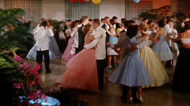 vidéos et rushes de 1960s wide shot young couples dancing at a formal prom under balloon decorations - romantisme