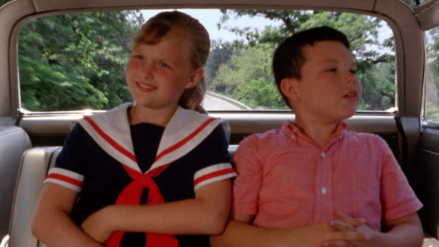 1960s wide shot young girl and boy riding in back seat of car, arguing - streiten stock-videos und b-roll-filmmaterial