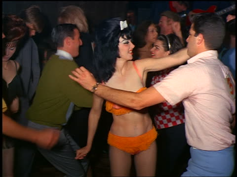 1960s woman in orange fringed bikini dancing with man amongst crowd indoors