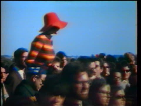 1960s woman in red hat sitting on shoulders of man in crowd marching in peace demonstration - sonnenhut stock-videos und b-roll-filmmaterial