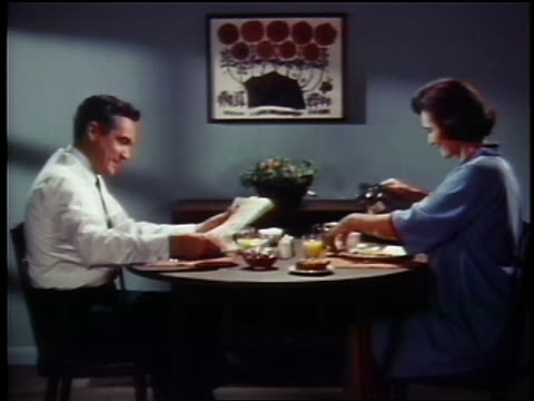 1960s woman pouring coffee for man at table / he eats toast + reads newspaper, she drinks juice - orangensaft stock-videos und b-roll-filmmaterial