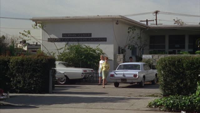 1960s ws women walking across parking lot - anno 1968 video stock e b–roll
