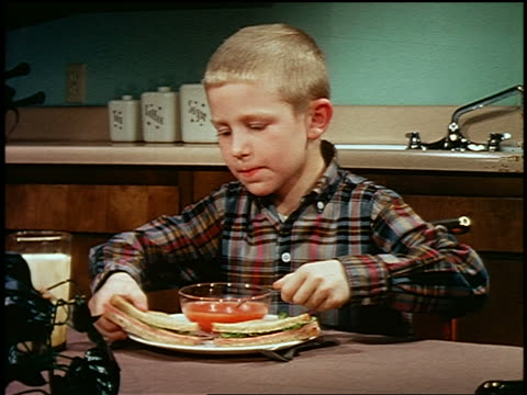 1960s young blond boy eating soup + sandwich at table in kitchen