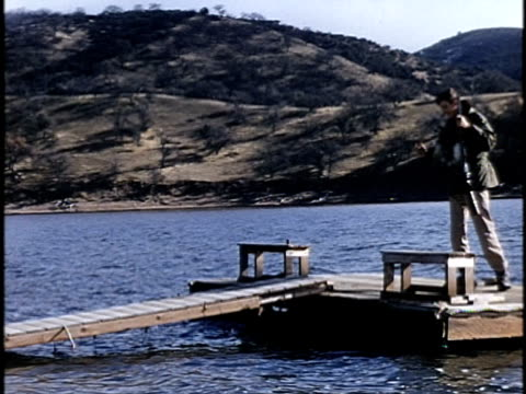 stockvideo's en b-roll-footage met 1960s ms pan young hunter with dead ducks on lake shore, lebec, california, usa - vogeljacht