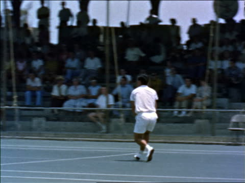 1960s young man serving tennis ball then hitting in volley in match with audience / educational