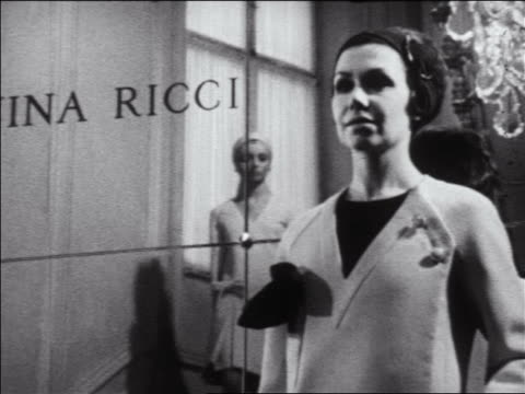 b/w 1960s zoom in to woman modeling coat + other woman in dress walking down stairs in mirror /nina ricci - steps and staircases stock videos & royalty-free footage