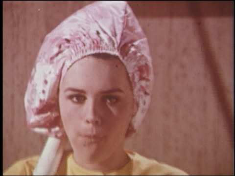 1960s zoom out from close up teen girl with hair dryer on head eating popcorn while watching television - grooming product stock videos & royalty-free footage