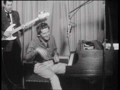 vídeos y material grabado en eventos de stock de b/w 1960s zoom out jerry lee lewis sitting at piano smiling on dj dewey phillip's radio show - instrumento de cuerdas