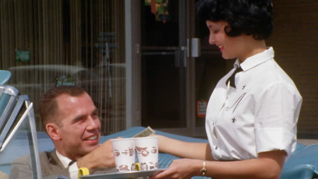 1960s zoom out medium shot carhop waitress bringing tray of drinks to man in convertible / man paying her