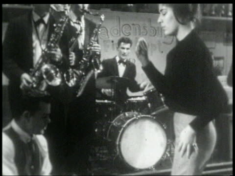 b/w 1960s zoom out teens dancing to rock band at high school dance - klassischer rock and roll stock-videos und b-roll-filmmaterial