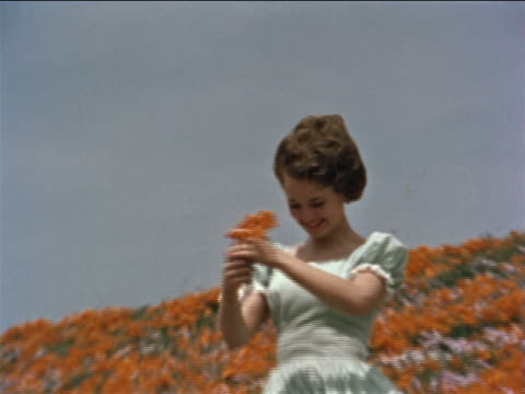 1960s zoom out woman holding flowers in wind + walking in field of flowers / California / educational