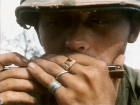 vídeos y material grabado en eventos de stock de 1960s1970s close up us soldier playing harmonica / vietnam - sólo hombres jóvenes