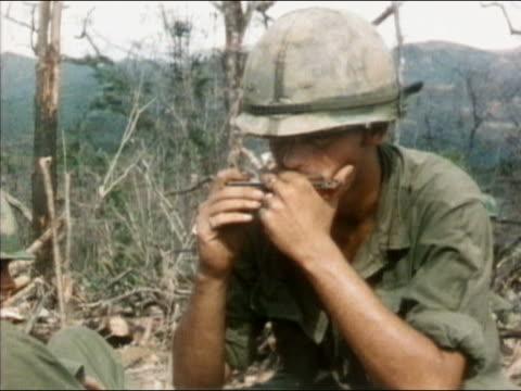 vídeos y material grabado en eventos de stock de 1960s-1970s medium shot us soldier playing the harmonica / vietnam - sólo hombres jóvenes